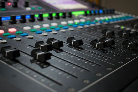 A professional music studio, with a mixing board and professional equipment
