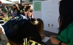 Students sign up for activities at Club Fair while leaders entice them with fun posters.