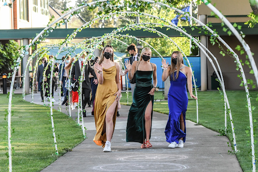 Seniors Eliza Collins, Josie Balish, and Lucy Langer walk down Mary's Way into Prom on May 15, 2021.